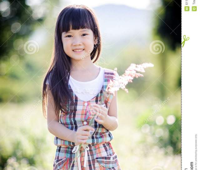 Vintage Color And Soft Focus Effect Little Cute Asian Girl In The Beautiful Dress Collecting Weed Grass Field Beside Road And Mountain Background