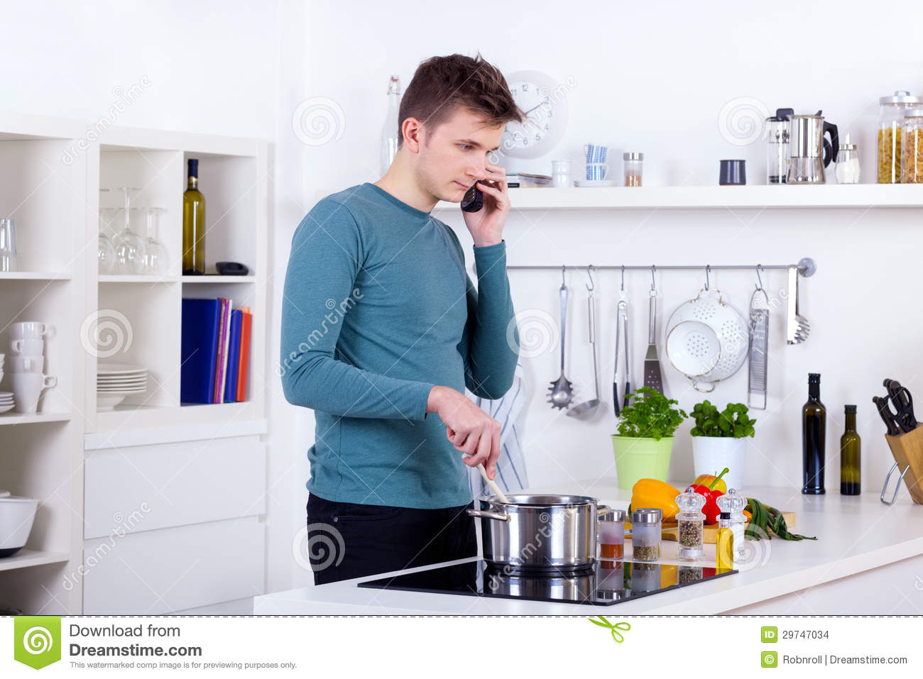 kitchen phone turquoise appliances young man cooking a meal and talking on the in his