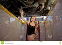 Young Brunette Mechanic In Checked Shirt Car Repair Pit