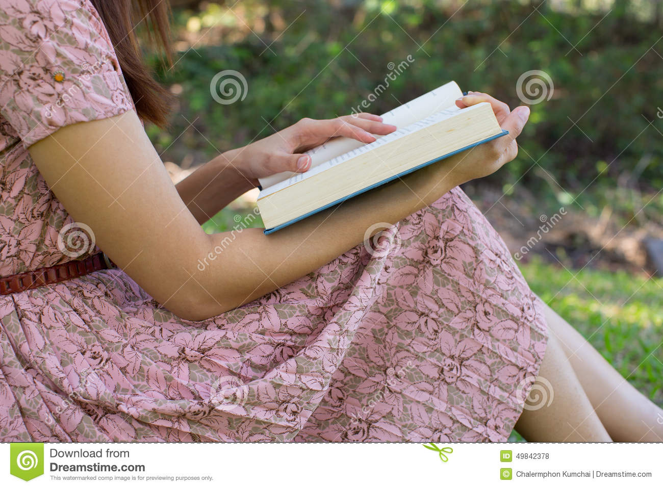 Young Woman Reading Bible In Natural Park Stock Photo