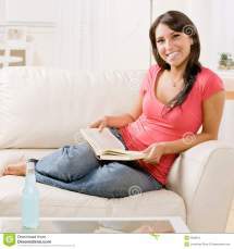 Young Woman Reading Book Sofa Home Stock