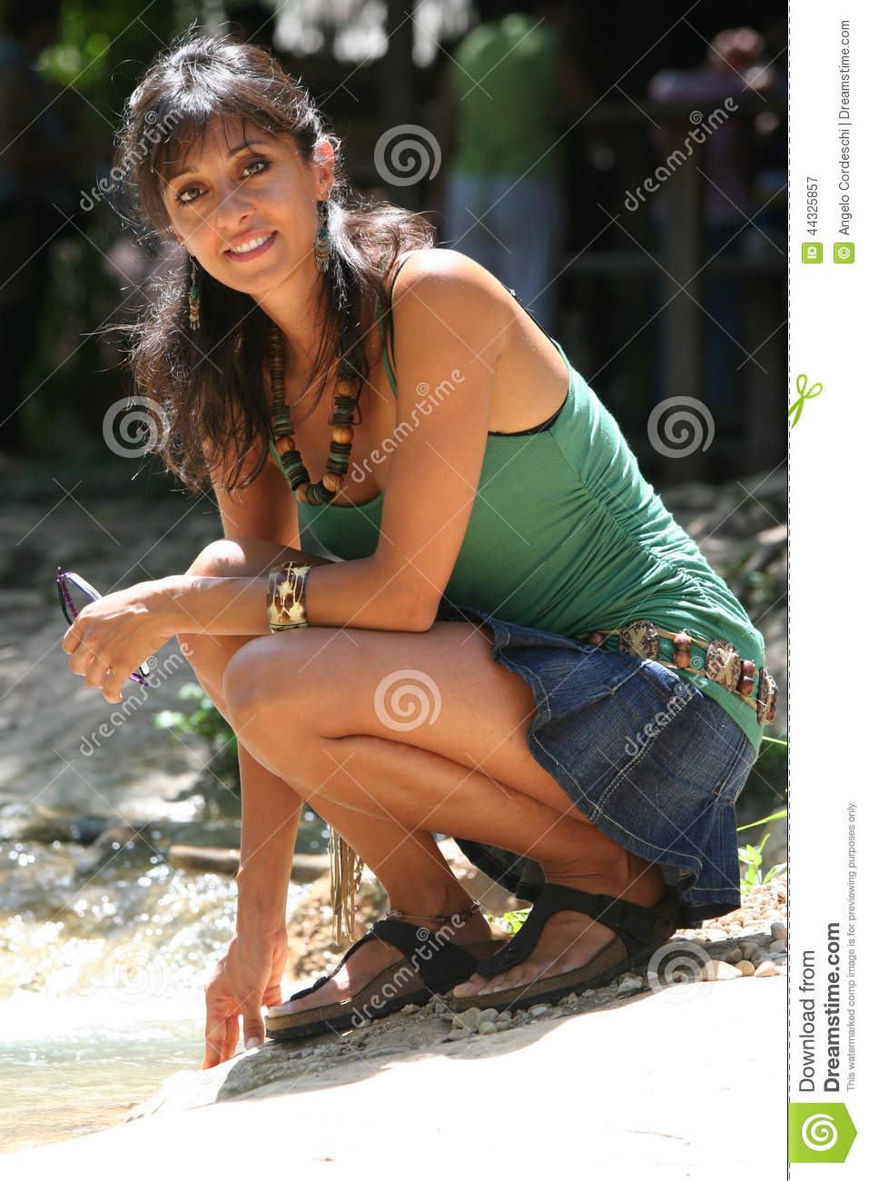 Young Woman Sitting Watching And Slight Smile Stock Photo