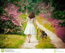 Young Woman Walking Barefoot With Dog Stock