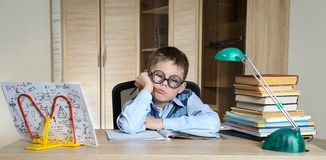 Tired Boy Wearing Funny Glasses Doing Homework. Child With Learning Difficulties. Boy Having Problems With His Homework. Education Royalty Free Stock Image