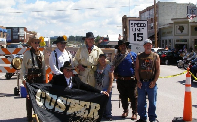 Locals in period costumes welcome visitors to the annual Custer Cruisin' event