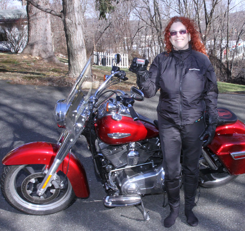 Shadow wearing the Firstgear women's Heated Jacket Liner, women's Heated Pants and holding the Remote Dual Heat Troller