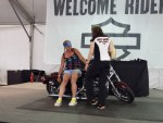 A Harley rep shows this lady how to pick up a downed scoot