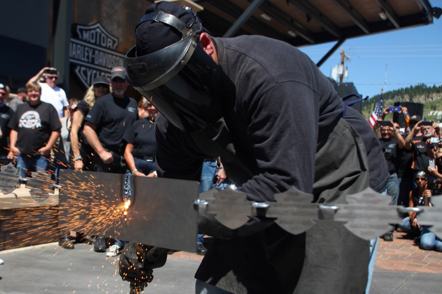 Showers of sparks as the chain snaps in two with bikes in the background. Photo courtesy of Toby Brusseau/AP Images for Harley-Davidson