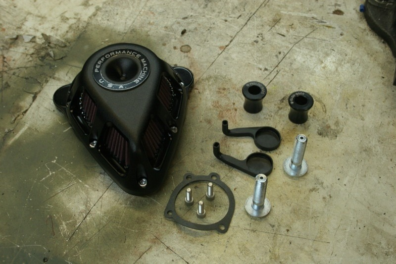 Out of the box is the air cleaner with backing plate, a mounting gasket, three bolts for mounting the air cleaner to the carb, two special breather bolts with two spacers, and a pair of breather ducts to keep crankcase vapors from leaving oily residue inside the body of the air cleaner