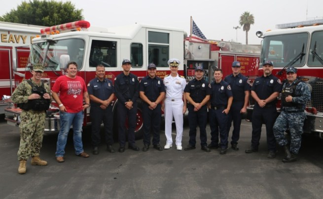 NBVC Chief Staff Officer Doug King (c.) flanked by Navy firefighters and police officers