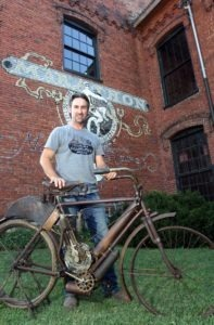 Mike stands with his rare 1904 Indian outside of the new shop in Nashville