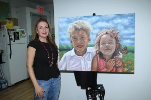 Elisa Seeger proudly displays the portrait painted by Seth Leibowitz showing her children Aidan and Sienna,