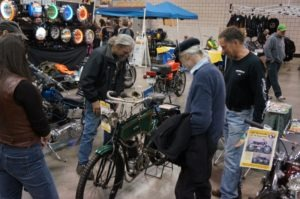 Visitors see what a 111-year-old motorcycle looks like as they gather around the 1902 Kerry, a motorcycle built in Belgium for the East London Rubber Company