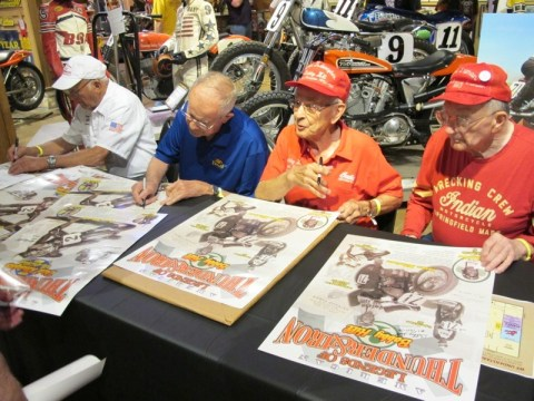"""Racing legends Dick """"King of the Beach"""" Klamfoth (far left), Bill Baird, Bobby Hill and Bill Tuman sign posters in the Dirt Track Heroes exhibit"""