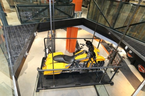 "H-D of NYC's ""taxi bike"" is showcased on the glass lift between the dealership's two levels"