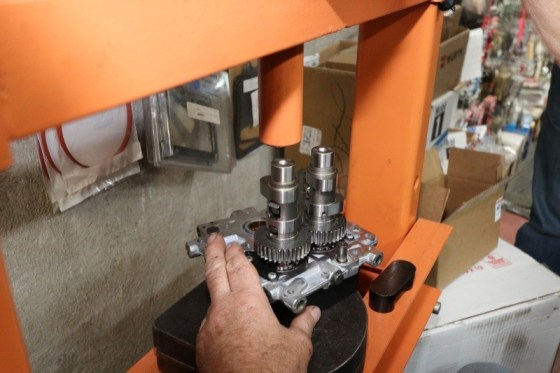 Ken uses a hydraulic press to install the cams into the cam plate