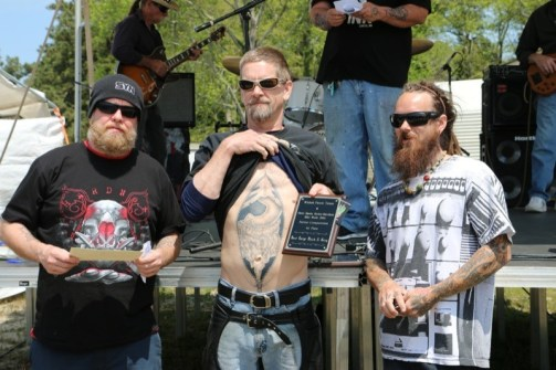 Kenny (l) and Buddy (r) from Wicked Parrot Tattoo present a plaque and gift certificate to Mike (center) from Grandy for best large black and white piece