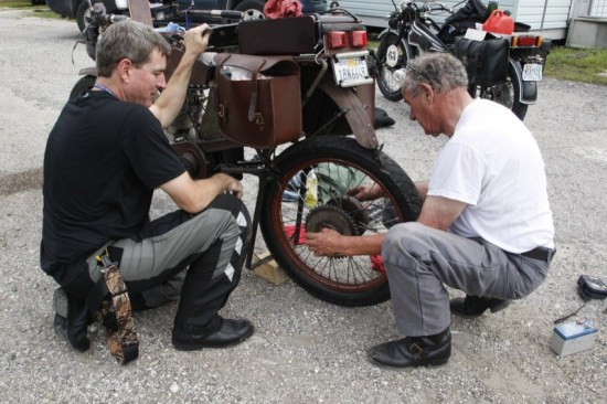 Victor Boocock gets a helping hand from Erik Bahl as he changes out a flat tire. The 1914 H-D was the oldest bike entered in the Cannonball Run.