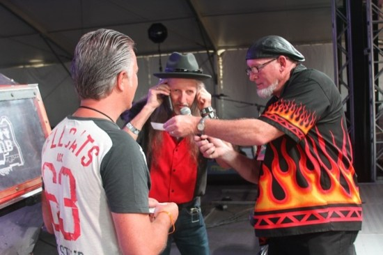 Harley-Davidson artist Scott Jacobs (l) and emcee Roy Riley (r) on stage with Pat Simmons of the Doobie Brothers as Pat calls the winner of the bike raffle