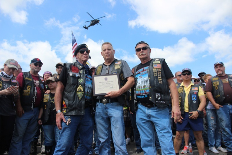 "Andrew ""Devildoc"" Mutchler, president of Hogs and Heroes, presents a plaque to Artie Muller, Director of Rolling Thunder"