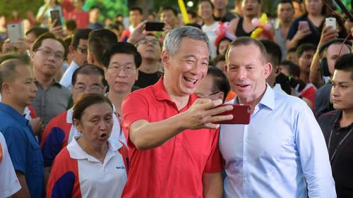 Singapore Prime Minister Lee Hsien Loong, left, shows Australian Prime Minister Tony Abbott, his phone  they took a walk in Bishan Park on Sunday, June 28, 2015 in Singapore. (AP Photo/Joseph Nair)