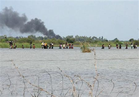 In this photograph released by the Sri Lankan military April 20, 2009 shows what the army says is thousands of people fleeing an area held controlled by the Tamil Tiger separatists in northeastern Sri Lanka. REUTERS/Sri Lankan Government/Handout