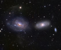 Galaxies - 2 Interacting Galaxies - The one on the right is being unraveled by the gravity of the other