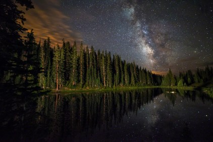 The Milky Way Galaxy over Lake Irene in Colorado. One would think it would be brighter in the middle, but the dark band in the middle is due to so much space dust that it actually obscures all the stars that are behind it.