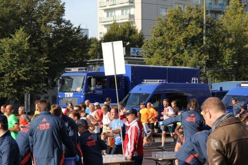 Läuferinnen und Läufer ziehen vor den THW-Fahrzeugen vorbei