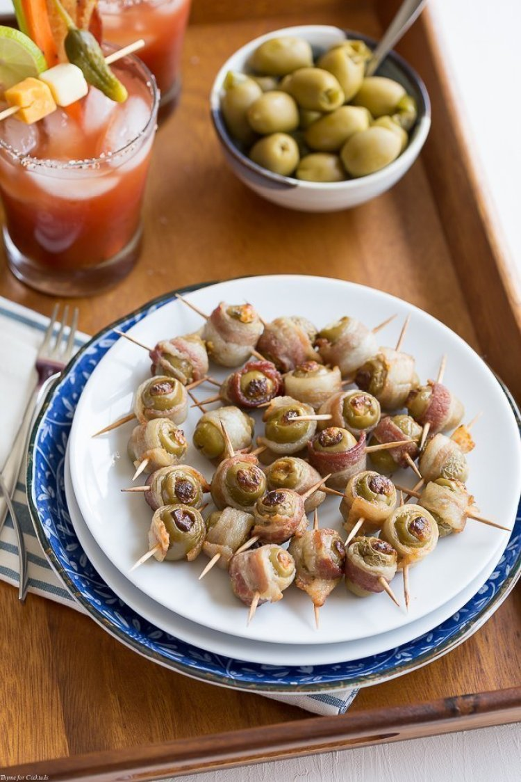Spicy Bacon Wrapped Olives - Green olives stuffed with jalapeno cream cheese mix then wrapped in bacon and baked until crispy!