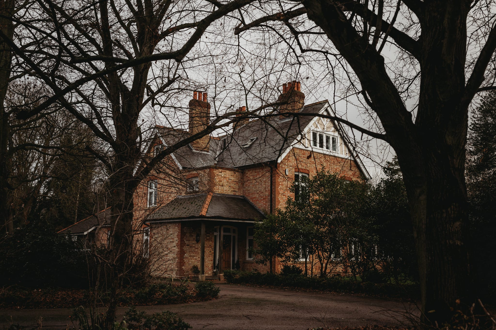 house surrounded by trees on a cloudy autumn day