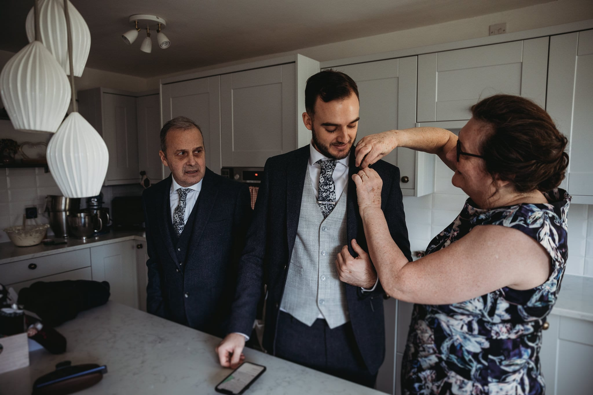 woman putting buttoniere on man's suit