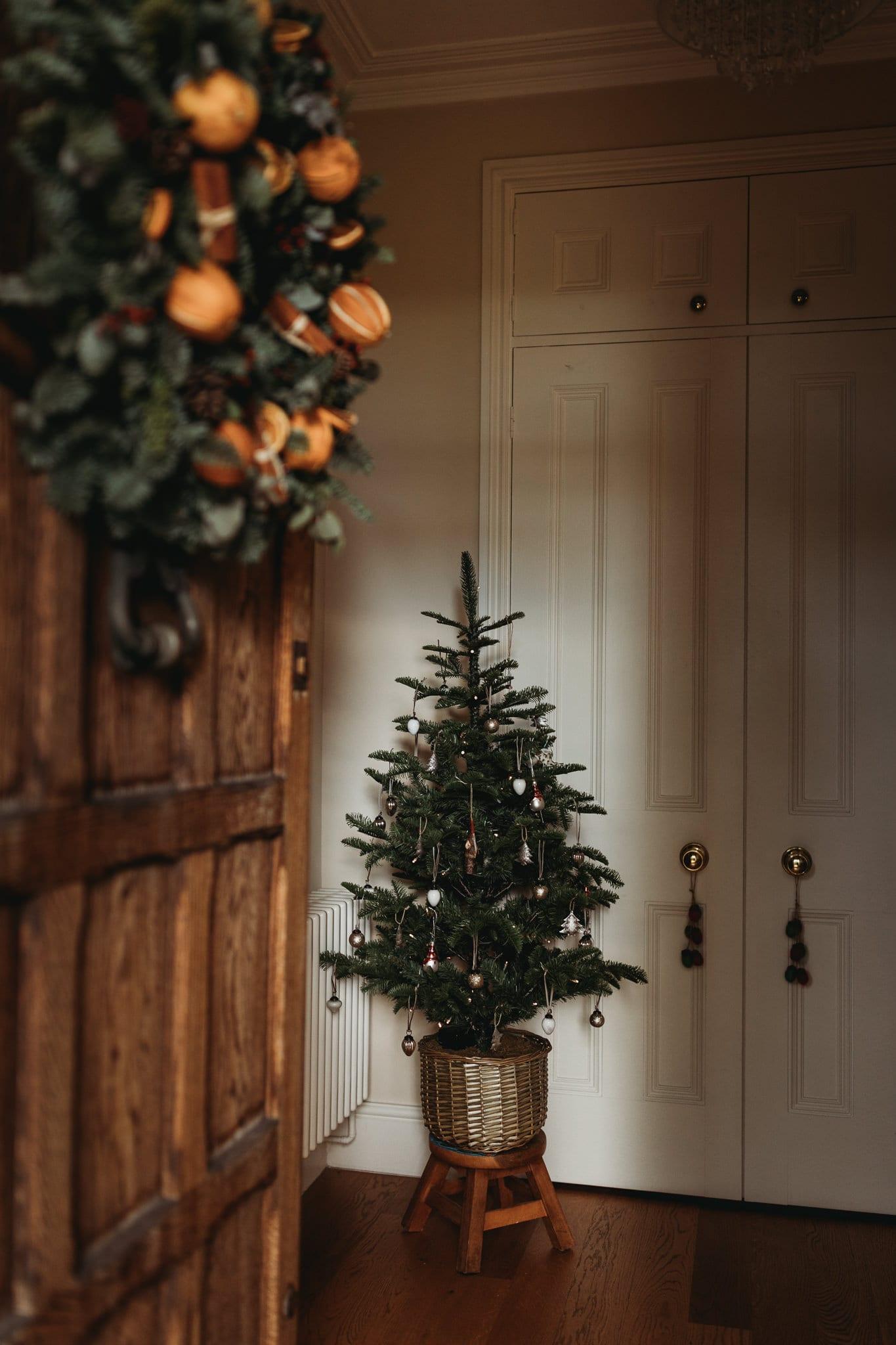 small Christmas tree on a stool, door is open, christmas wreath is hanging on door