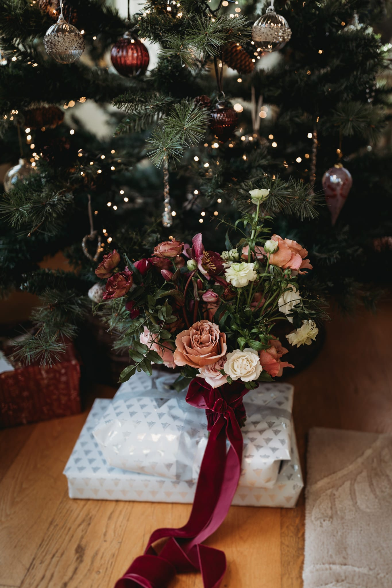 closeup of a bridal bouquet, christmas tree in background