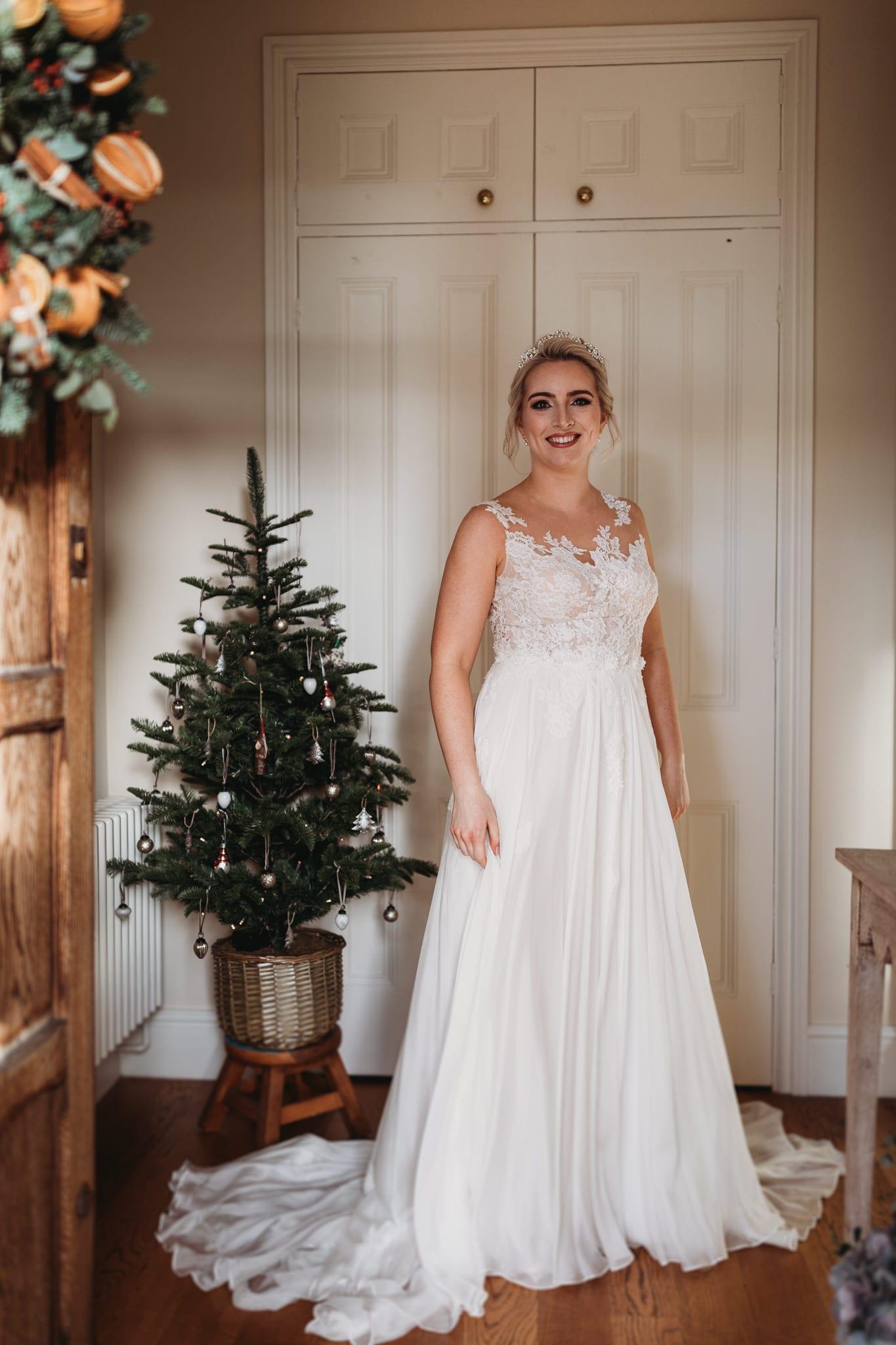 bride standing in hallway, door open, mini christmas tree in background on a stool