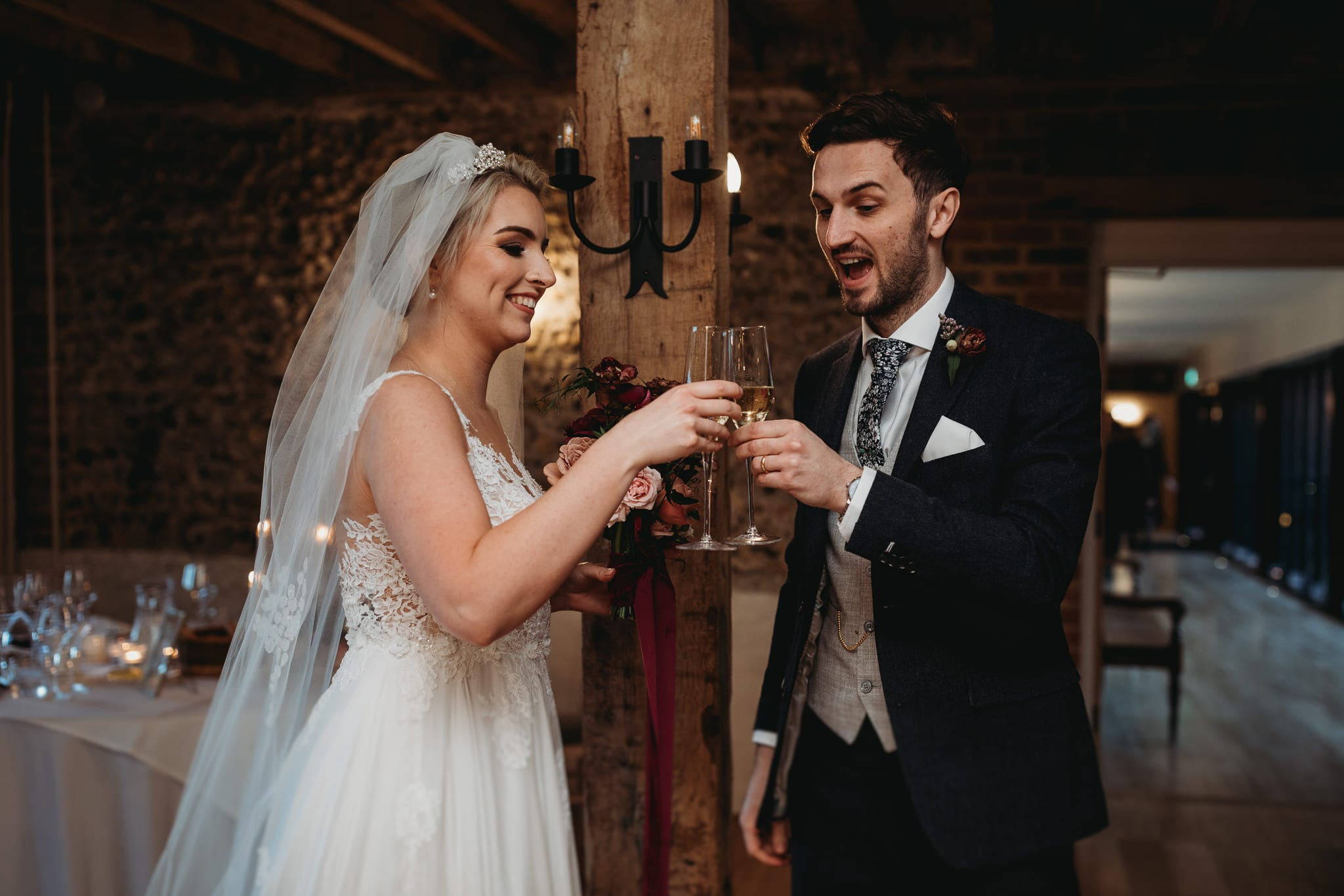 bride and groom holding champagne glasses looking happy at Granary Estates Intimate wedding