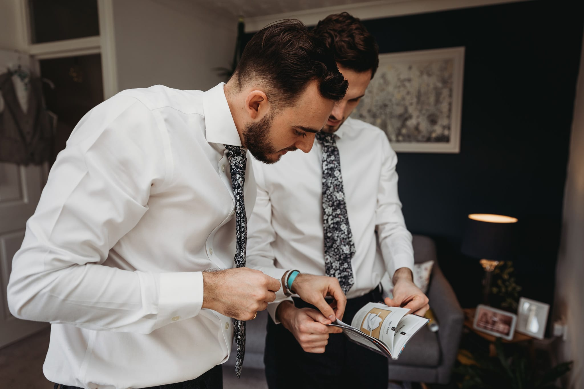 groom and best man looking at a book