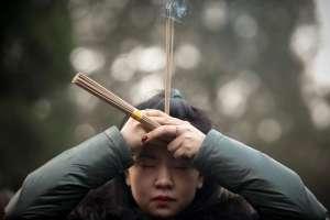Une femme brûle des bâtons d'encens, photographie Thomas Peter