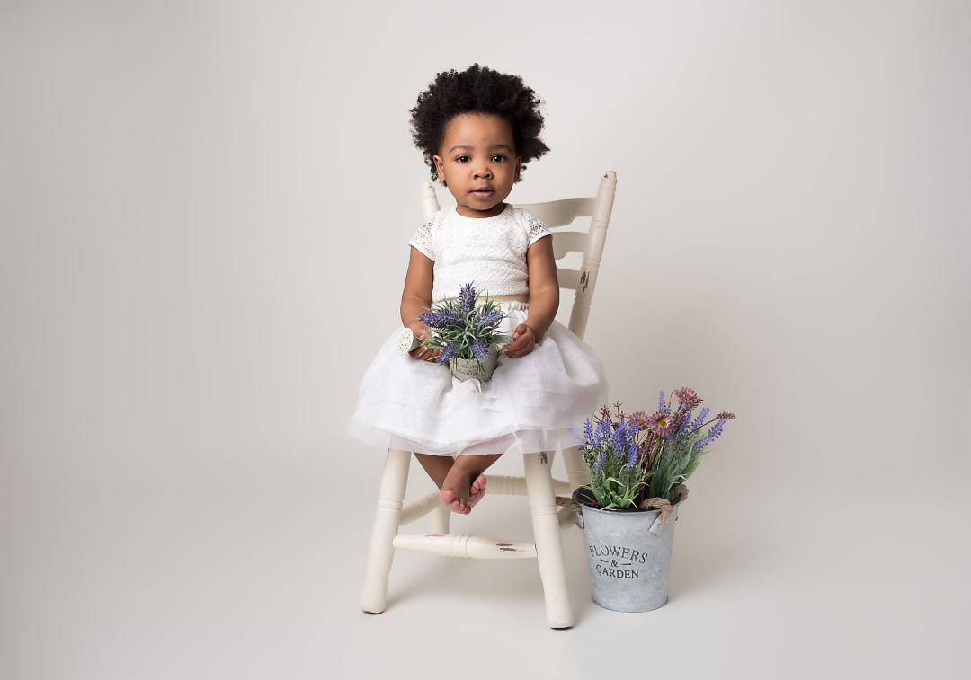 Toddler Posed on a white chair holding lavender