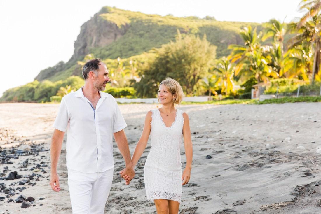 Un couple qui marche sur la plage au lever du soleil lors d'une séance photo de famille à la Réunion