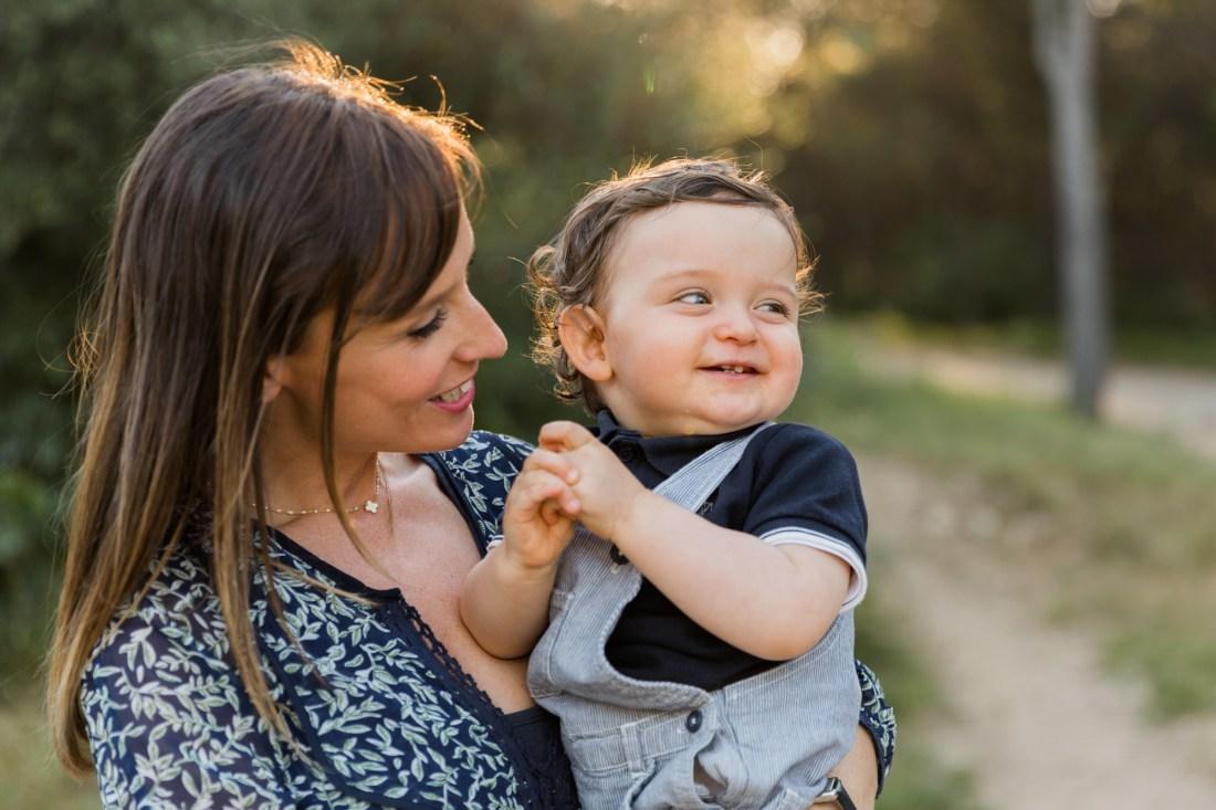 Un bébé d'un an souriant dans les bras de sa maman