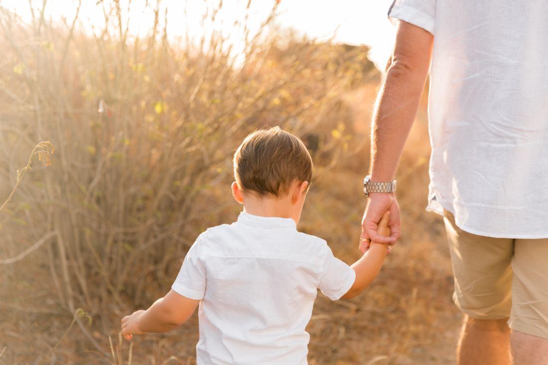 Un petit garçon tenant la main de son papa lors d'une séance photo en famille sur l'île de la Réunion