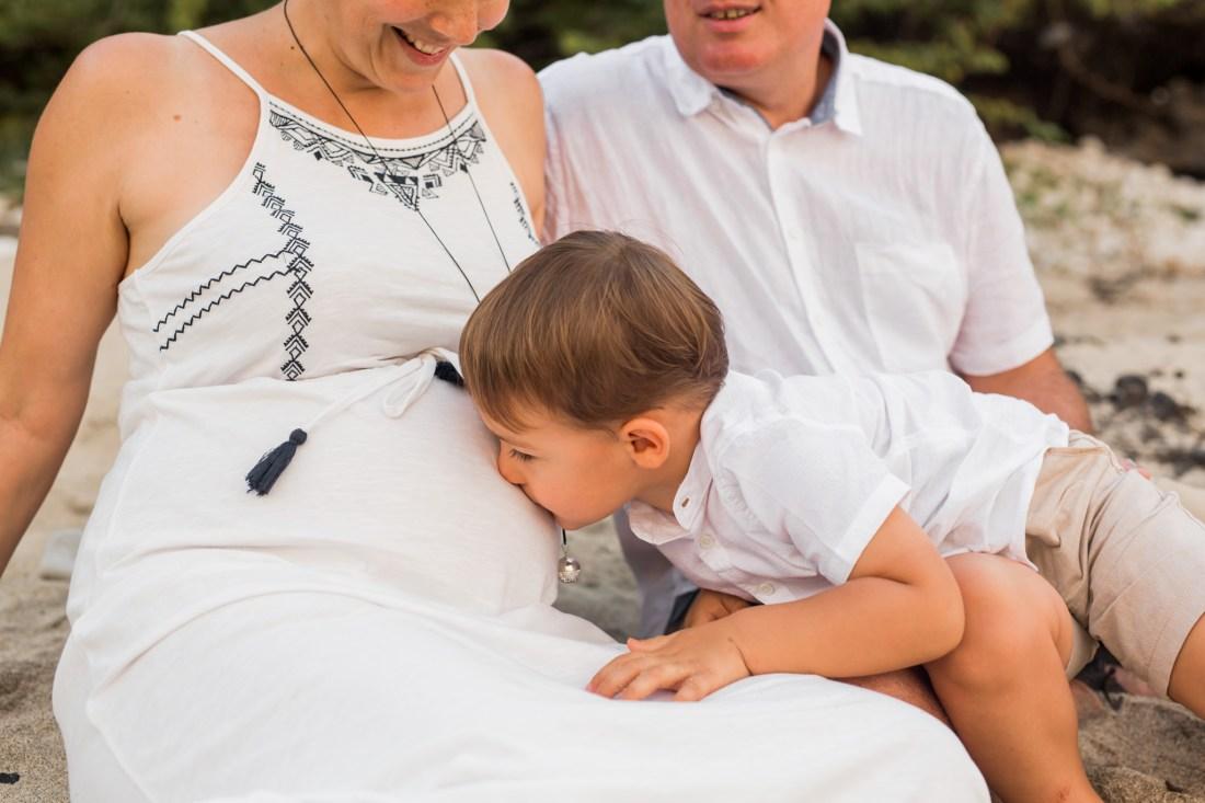 Un petit garçon qui embrasse le ventre de sa maman enceinte sur une plage