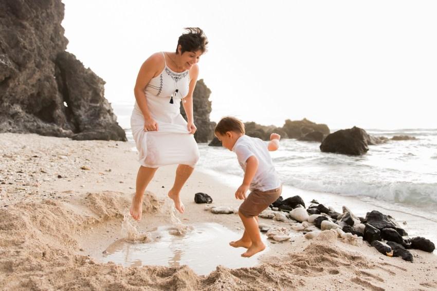 Une maman et son fils qui sautent dans l'eau sur une plage de la Réunion pendant une séance famille