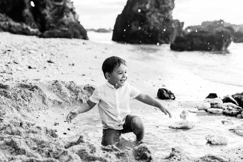 Une photo en noir et blanc d'un petit garçon qui joue dans l'eau sur une plage de la Réunion