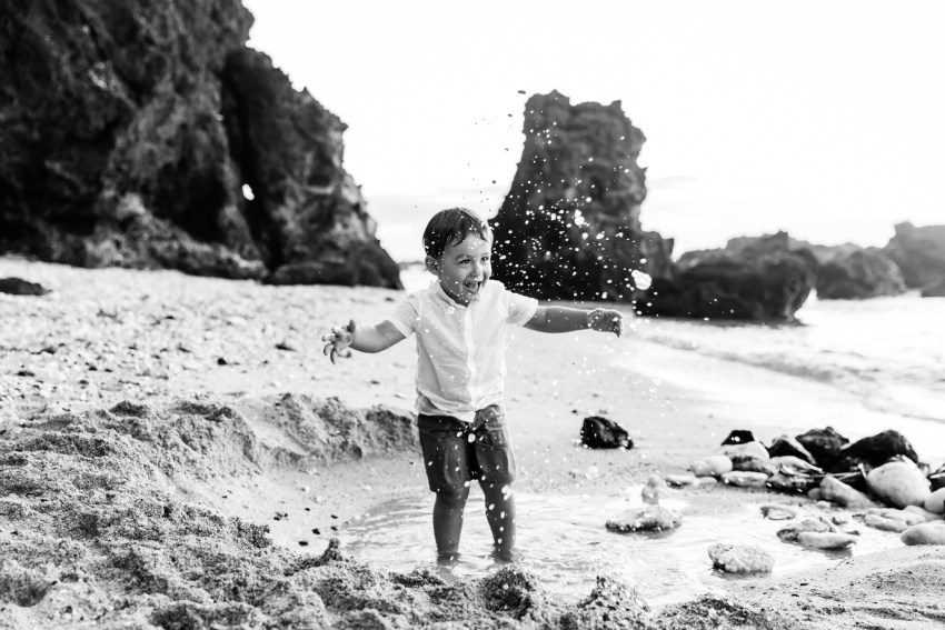 Un enfant qui s'amuse dans l'eau sur une plage de l'île de la Réunion lors d'une séance famille