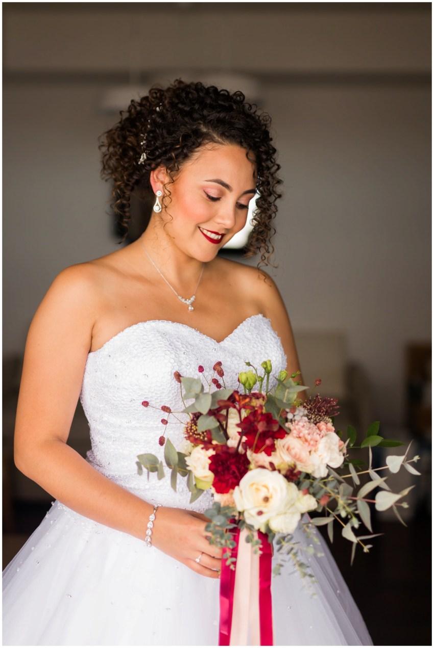 Une belle mariée et son bouquet de fleur dans les tons rose poudré marsala