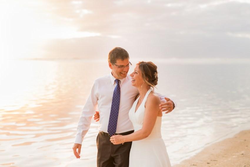 Un couple qui rigole sur la plage après leur renouvellement de voeux de mariage