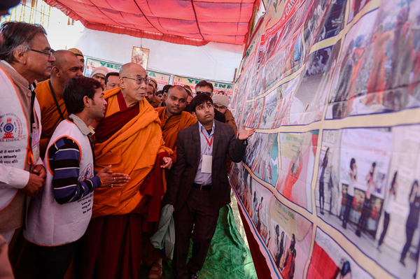 His Holiness the Dalai Lama looking at an exhibit of the activities of ...