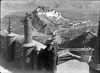 Monks blowing radung , Potala in distance